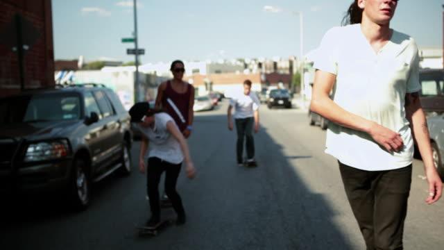 skateboarders skating in the street - stunt stock-videos und b-roll-filmmaterial