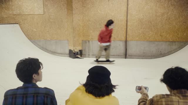 ランプに乗って彼らの友人の写真を撮るスケートボーダー(スローモーション) - スケートボード点の映像素材/bロール