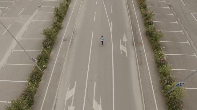 vidéos et rushes de vue aérienne le skate sur une aire de stationnement - transport aérien
