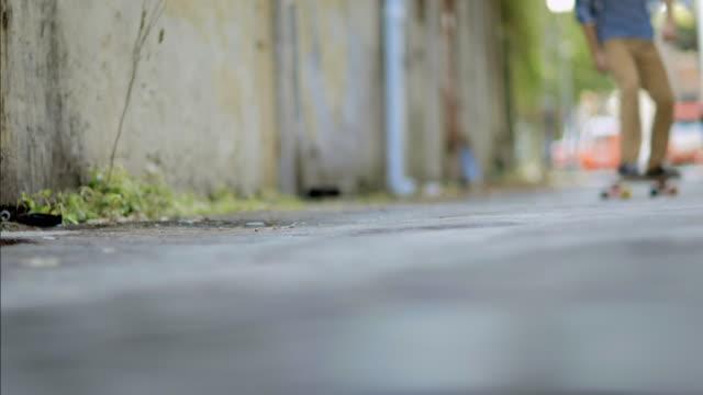 vídeos y material grabado en eventos de stock de skater cruises through downtown alleyway on longboard - pasear en coche sin destino