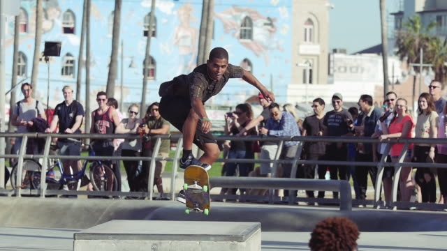 stockvideo's en b-roll-footage met skater doing trick at venice beach skate park, los angeles - skateboardpark