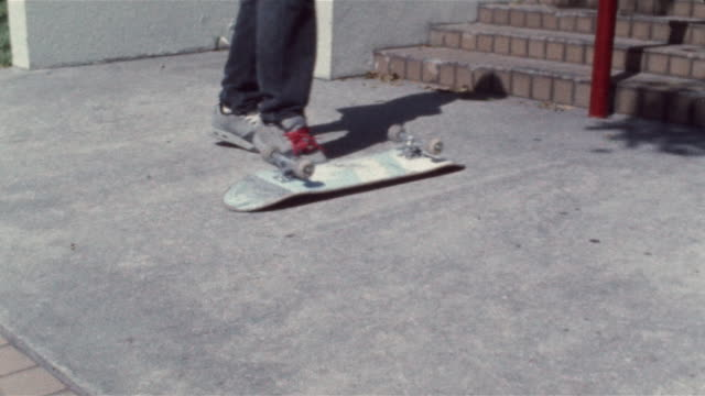 Skater kicking and flipping overturned skateboard and carrying board off frame