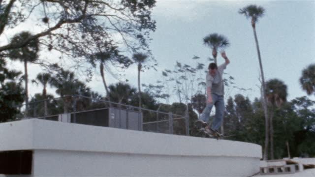 vídeos de stock e filmes b-roll de skater ollieing off jump ramp onto loading dock and tailsliding along edge - só um menino adolescente