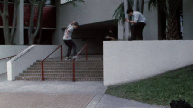 skater ollieing onto and sliding down handrail as friends film him - 階段点の映像素材/bロール