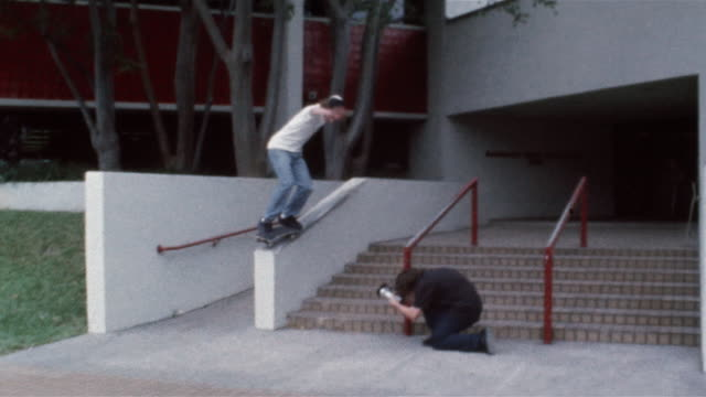 skater ollieing onto and sliding down railing as friend films him - railing stock videos & royalty-free footage