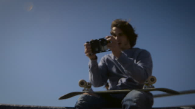 skater sitting on dog bowl looking at his phone and filming in venice skatepark california