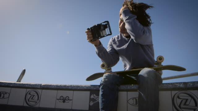 skater sitting on dog bowl looking at his phone venice california skatepark