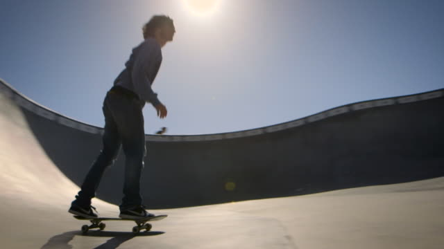 skater skates in dog bowl around camera venice california skatepark - un ragazzo adolescente video stock e b–roll