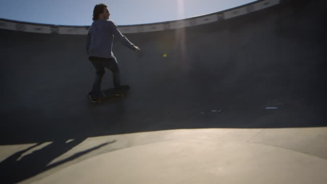 skater skating through dog bowl in venice california skatepark - un ragazzo adolescente video stock e b–roll