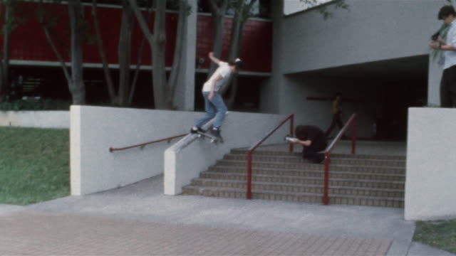 stockvideo's en b-roll-footage met skater sliding down handrail / falling off skateboard - tienerjongens