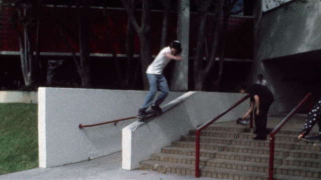 skater sliding down railing and falling onto rear end as friend films him - stunt stock videos & royalty-free footage