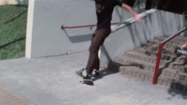 skater sliding down railing and wiping out as friend films him / grabbing foot in pain - 滑る点の映像素材/bロール