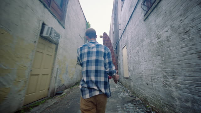 skater walks down urban alleyway carrying custom longboard overhead - gasse stock-videos und b-roll-filmmaterial