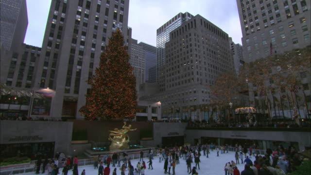 ha skaters ice skating at rink in rockefeller plaza / new york city, new york, united states - rockefeller center christmas tree stock videos & royalty-free footage