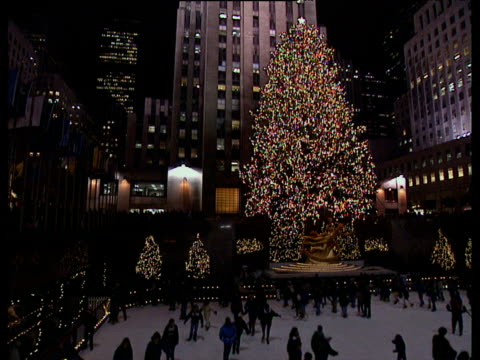 vidéos et rushes de skaters on ice-rink at rockefeller plaza with large xmas tree in background - de grande taille