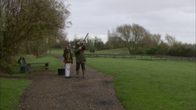 a skeet shooter fires his shotgun toward the sky. - tontaubenschießen stock-videos und b-roll-filmmaterial