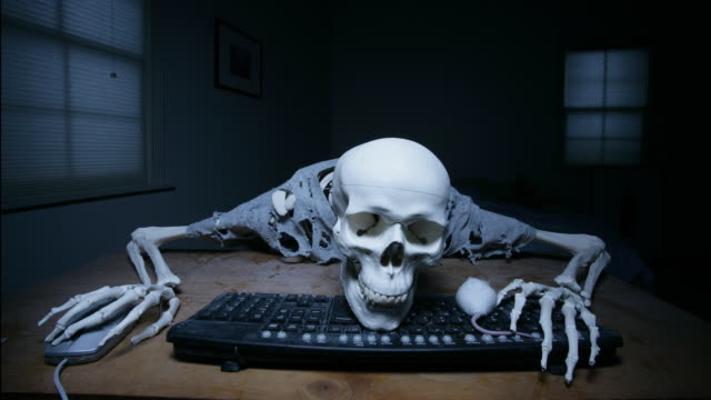 A skeleton at a keyboard with a real mouse