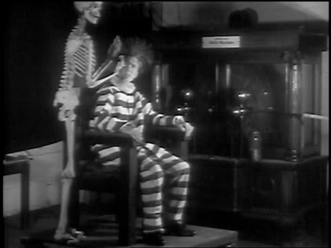 b/w 1936 skeleton standing next to man sitting in chair with prison uniform + hair standing on end - electric chair stock videos & royalty-free footage
