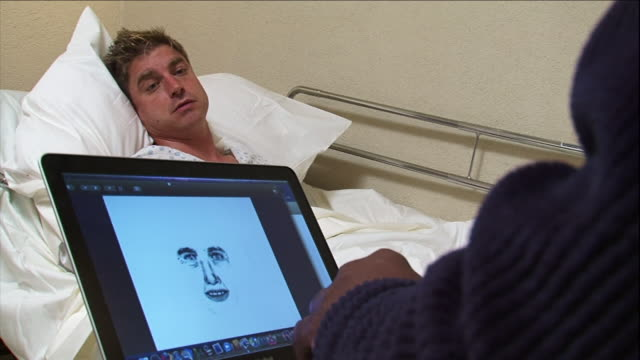 stockvideo's en b-roll-footage met a sketch artist works on a computer while a male patient lies in a hospital bed. - slachtoffer