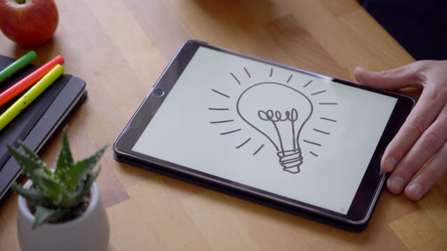 sketching a lightbulb for creativity - table top view stock videos & royalty-free footage