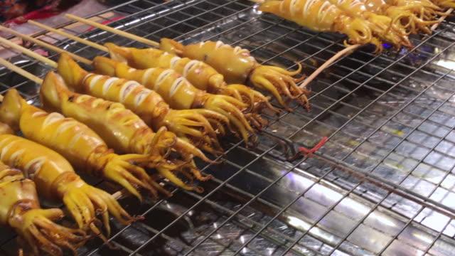 Skewered squid on wooden stick , Bangkok , Thailand