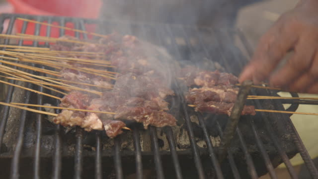 Skewers of meat are placed on a barbecue.