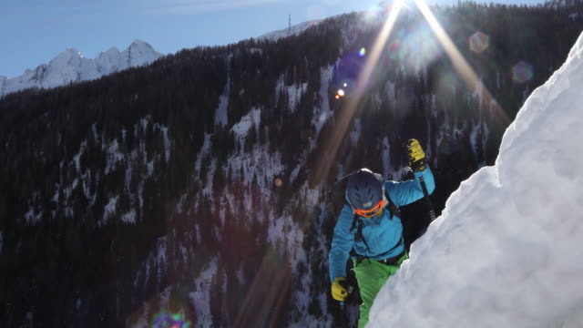 vídeos y material grabado en eventos de stock de alpinista de esquí sube la cuesta empinada de nieve sobre las montañas - chaqueta de esquiar