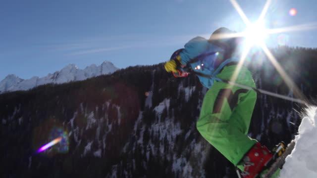 lo scialpinista sale sulla ripida pista da neve sopra le montagne - bastoncino da sci video stock e b–roll