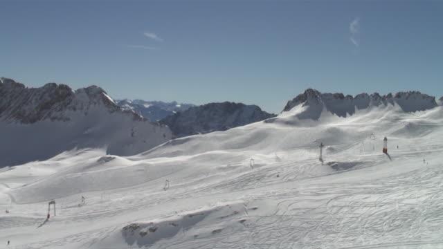 ws pan ski arena on zugspitzplateau, skiing lifts and mountain panorama / garmisch, bavaria, germany - garmisch partenkirchen stock videos and b-roll footage