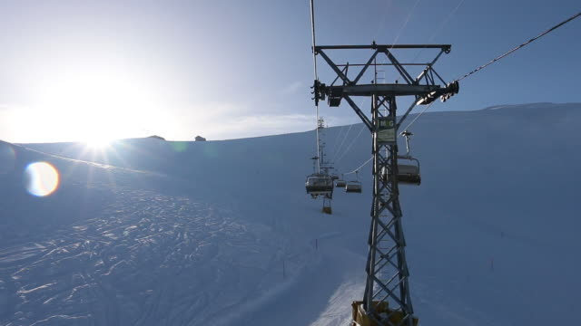 ski chairlift ascends ski slope, winter snow - alpi video stock e b–roll