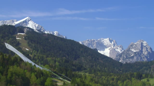 pan ski jump in front of bavarian alps - textfreiraum stock videos & royalty-free footage