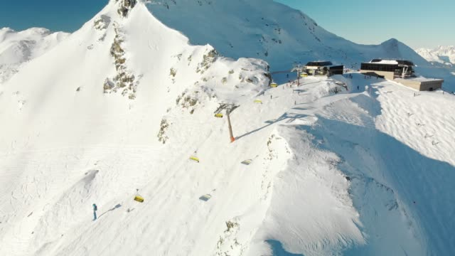 ski lift almost at the top of the mountain - droone shot - ski flying stock videos and b-roll footage