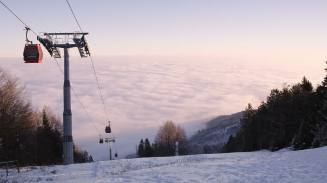 4K Ski lift gondolas above clouds and snowy landscape, real time