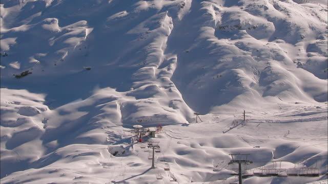 A ski lift operates on a snowy mountain.