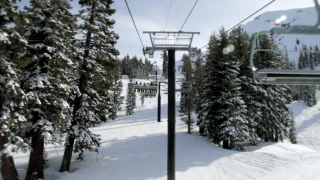 ws pov ski lift riding over snowy hill at ski resort, skier skiing in background / squaw valley, california, usa - seggiovia video stock e b–roll