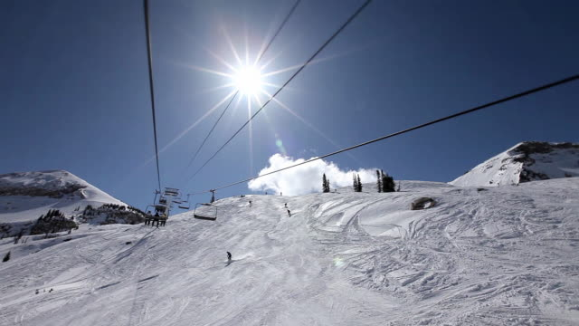 ws pov ski lift riding over snowy mountain at ski resort on clear sunny day / alta, utah, usa - utah stock videos & royalty-free footage