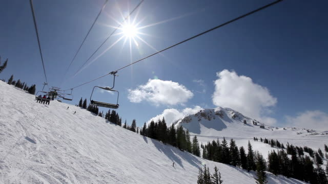 ws pov ski lift riding over snowy mountain at ski resort on clear sunny day / alta, utah, usa - ski lift point of view stock videos & royalty-free footage