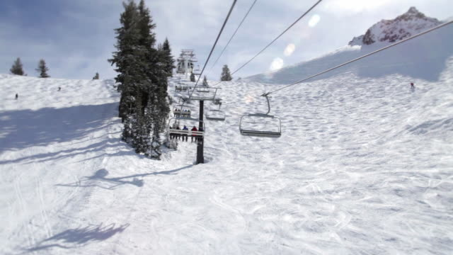 WS POV Ski lift riding over snowy mountain at ski resort / Squaw Valley, California, USA