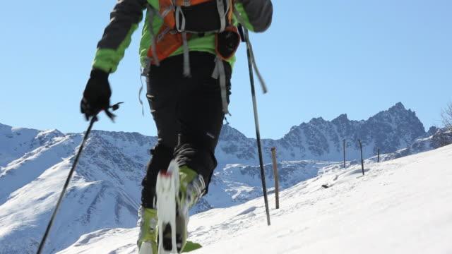 ski mountaineer ascends snowslope towards distant mtns - bastoncino da sci video stock e b–roll