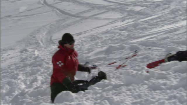 vidéos et rushes de a ski patrol team digs in a snowy slope. - secouriste