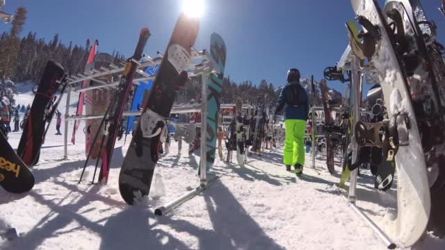 ski racks full of skis and snowboards at a ski resort. - urlaubsort stock-videos und b-roll-filmmaterial