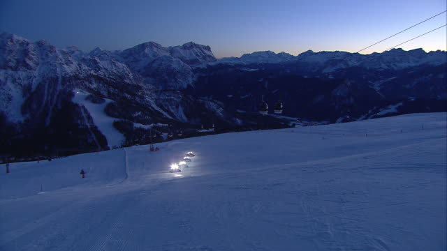 Ski resort by night, moutain scenery in the background