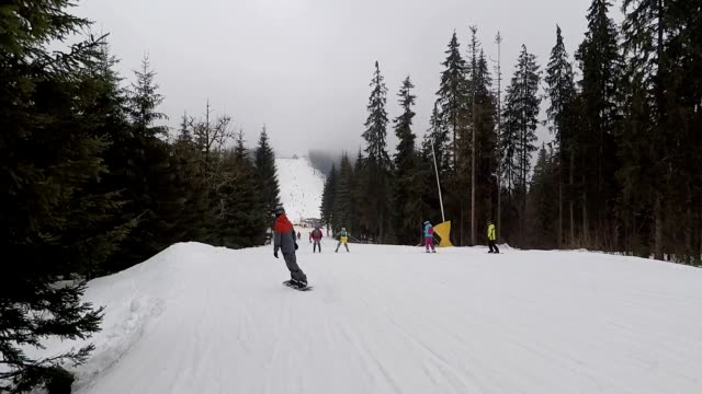 Ski slope with snowboarders and skiers.