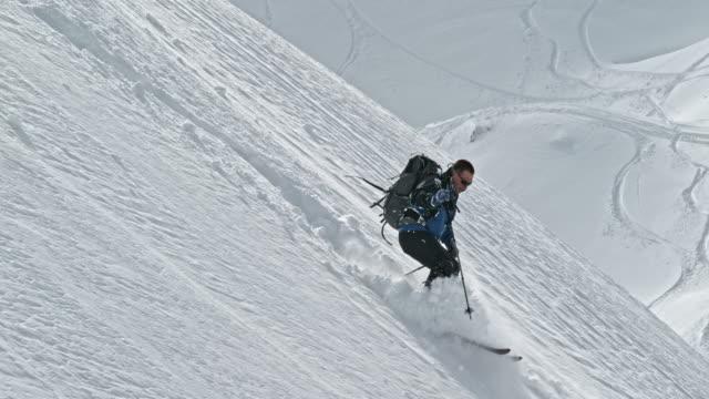 SLO MO Ski tourer descending the mountain in sunshine