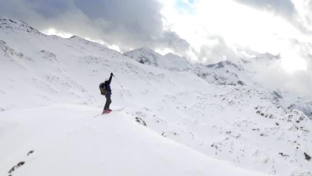 Freistil-Skifahren tourer raising hands auf den Besiegten mountain top