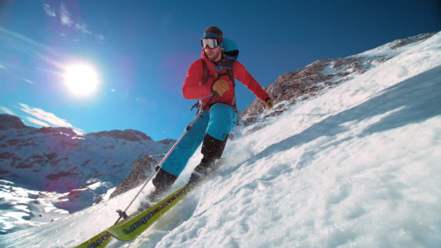 slo mo ts ski tourer skiing down the mountain - leisure activity stock videos & royalty-free footage