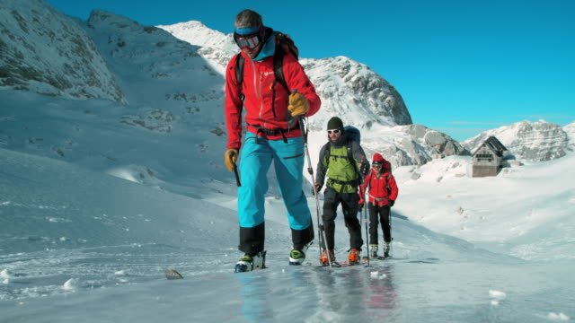 ski tourers ascending the icy slope on a sunny day - skiing and snowboarding stock videos and b-roll footage