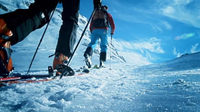 Ski tourers progressing up the mountain on sunny day
