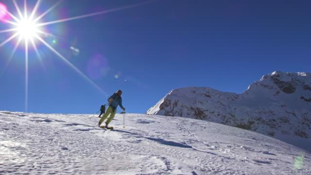 SLO MO Ski tourers skiing down a mountain slope in sunshine