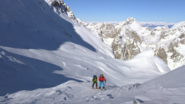 pan ski touring on a sunny day in the mountains - uphill stock videos & royalty-free footage
